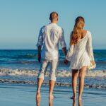 couple se tenant la main sur une plage