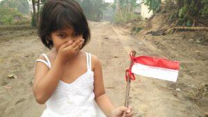 petite fille tenant un drapeau indonésien